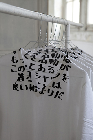 you can't read this T from a distance… the message [in Japanese] is meant to encourage the wearer to explain to explain.A percentage of the sales benefits 'AIDES', a French organization dedicated to fight the HIV virus and take care of patients living with HIV/AIDS www.aides.org . Over the years, 170,000 T-shirts have been sold and brought a contribution of over 700,000 euros to 'AIDES'.